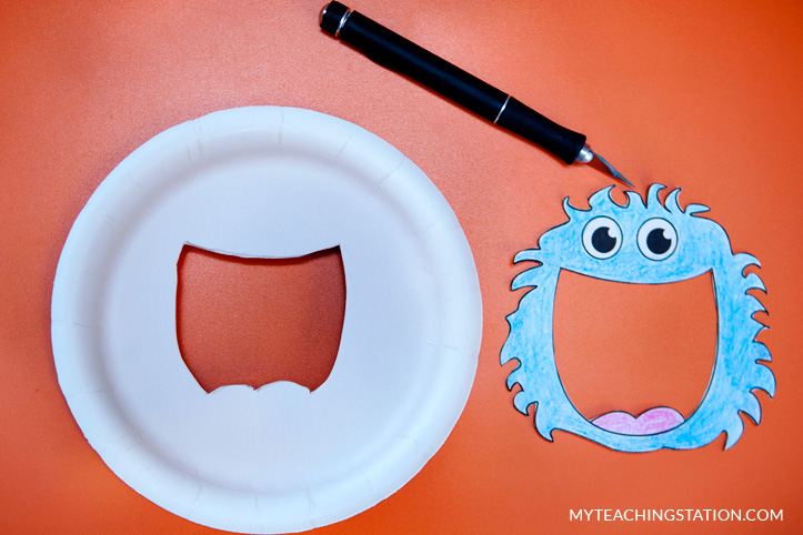 Cut paper plate to make alphabet finder magnifying glass.